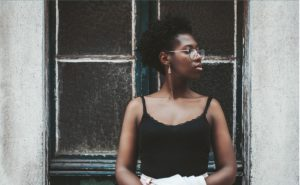 black woman with glasses standing in front of a window