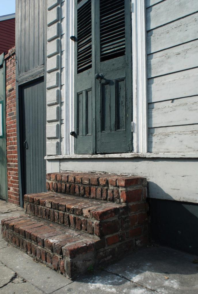 brick stoop of shotgun house with green shutters
