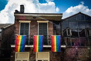 bourbon street house with three pride flags hanging from balcony