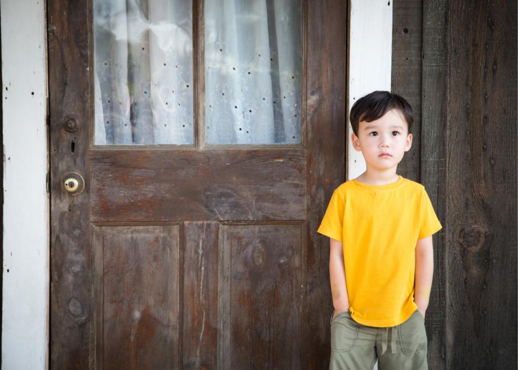 little boy in yellow shirt in front of brown door