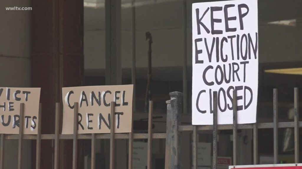 """fence with handwritten signs that say """"cancel rent"""" and """"keep eviction court closed"""""""