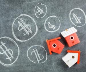 dollar signs drawn on a chalkboard next to three orange and white birdhouses