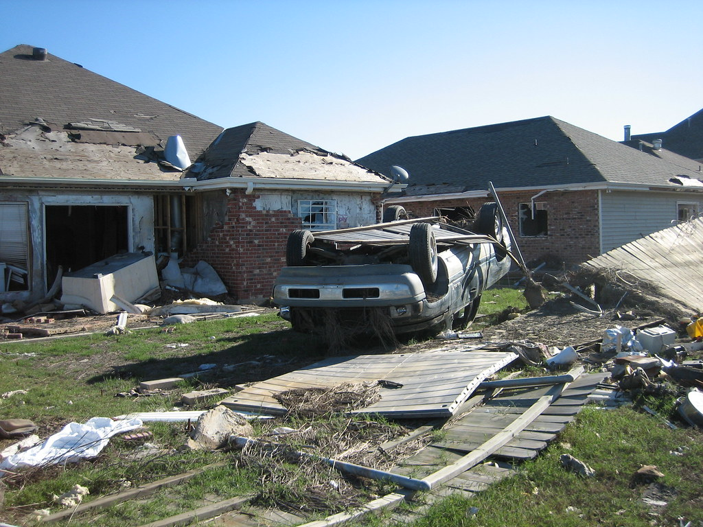 overturned car in front of house destroyed by hurricane