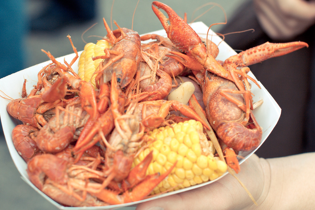 paper bowl with boiled crawfish and corn on the cob