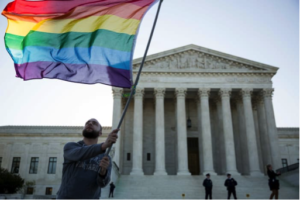 Man standing in front of the Supreme Court, waving a Pride flag.