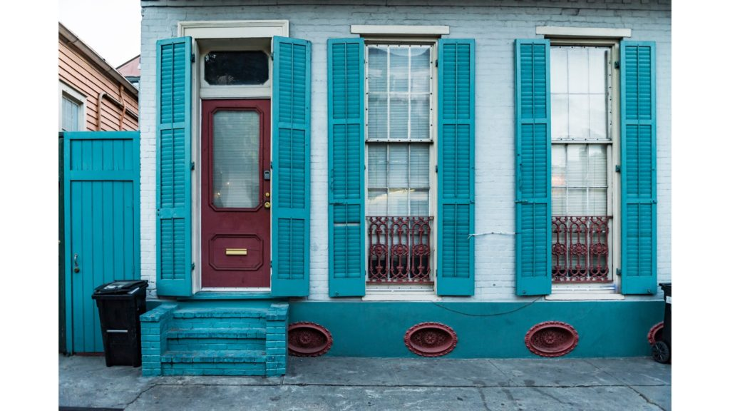 Blue colored New Orleans home with shutters