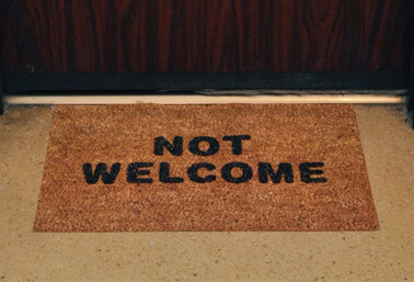 """welcome mat by door that has """"not welcome"""" printed on it"""