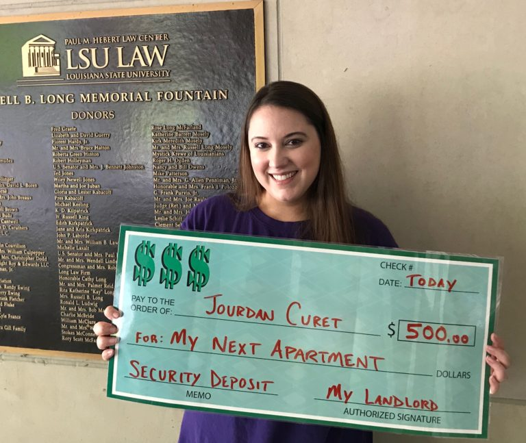 A woman, Jourdan Curet, holding giant check that says Security Deposit for my next apartment, $500