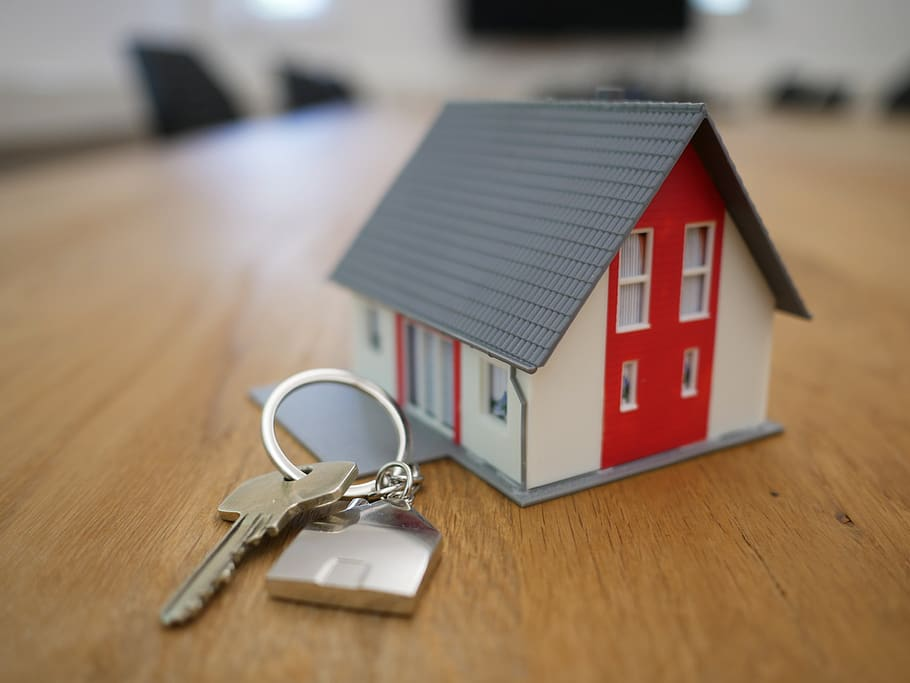 key resting beside tiny model of a house on wooden table