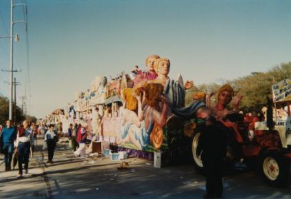 mardi gras float with people walking beside it