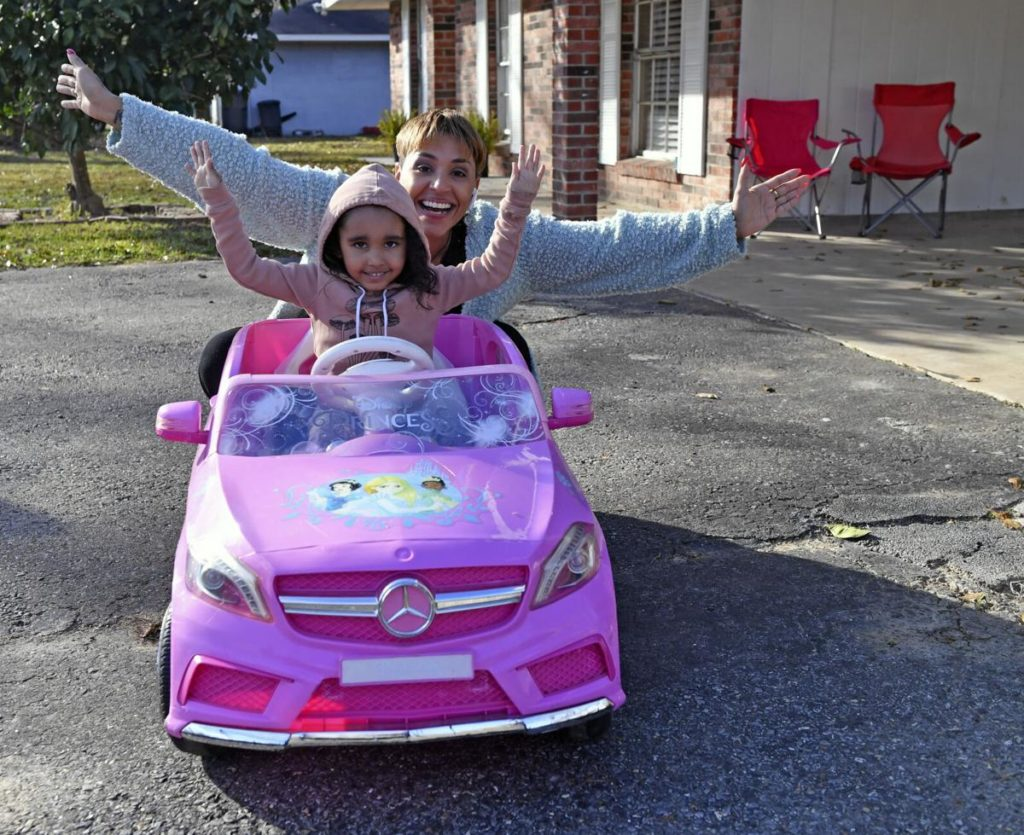 Smiling young girl in pink toy car with arms up. Her mother is behind her with her arms up in joy as well. Arielle Butler and her daughter, who were denied an apartment in Zachary, LA due to an eviction record related to unemployment during COVID-19. Source: Hilary Scheinuk, The Advocate.