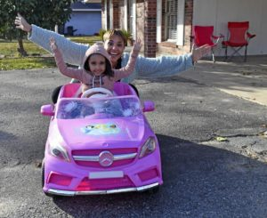 Smiling young girl in pink toy car with arms up. Her mother is behind her with her arms up in joy as well. Arielle Butler and her daughter, who were denied an apartment in Zachary, LA due to an eviction record