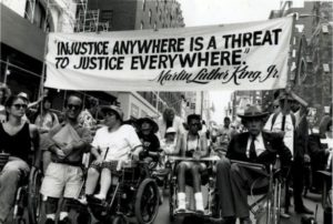 black and white image of protesters in wheelchairs with a banner that says