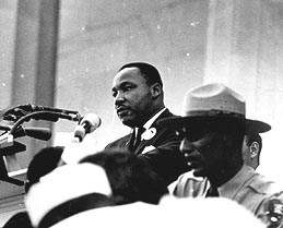black and white image of mlk, jr. at a podium about to speak, he's standing next to an african american police officer