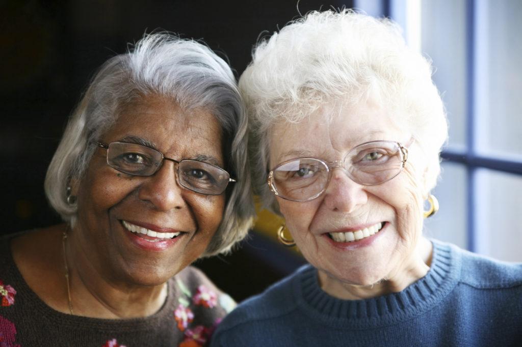 Two older women friends, both wearing glasses