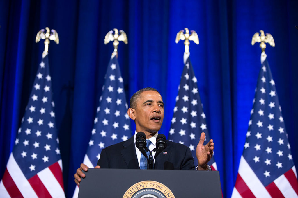 President Barack Obama speaking at a podium in front of four u.s. flags