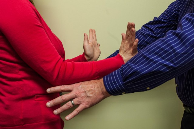 woman in red shirt trying to stop man in blue shirt from grabbing her