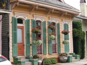 orange shotgun house with green shutters and hanging plants
